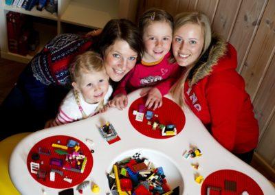 En familie som bygger LEGO i byggerommet på Byggehytta LEGO